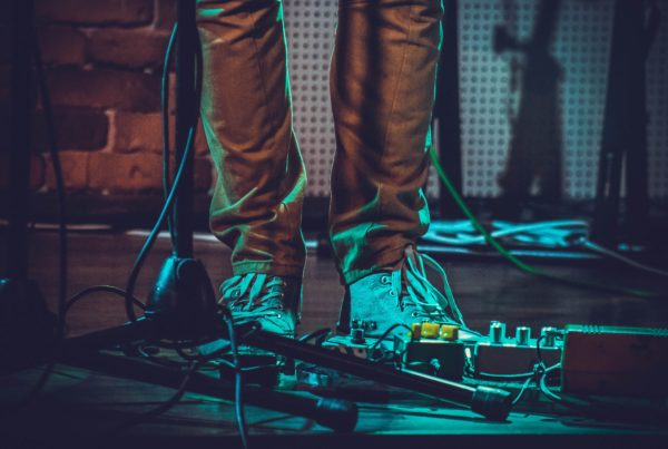 Man standing in front of a pedal board during a live gig